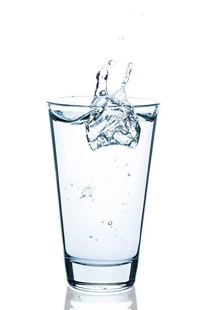 sprudelndes glas wasser mit spritzer und tropfen - wasser stock pictures, royalty-free photos & images