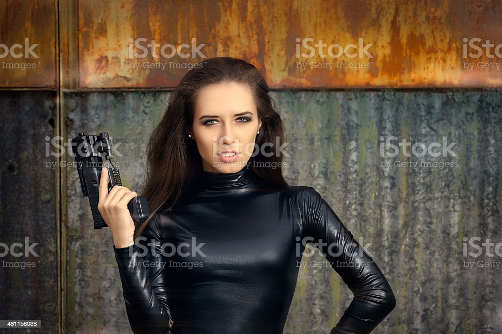 Spy Agent Woman in Black Leather Suit Holding Gun stock photo