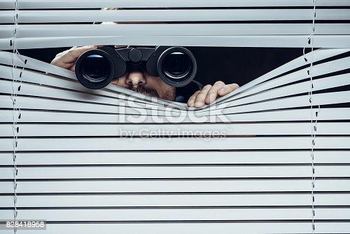 Spy at work. Man with binoculars.