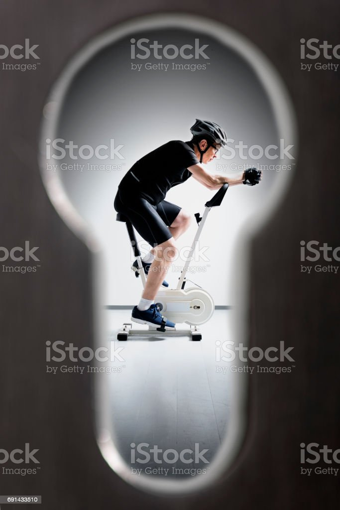 Spying Through The Keyhole  On a Guy Riding An Exercise Bike stock photo