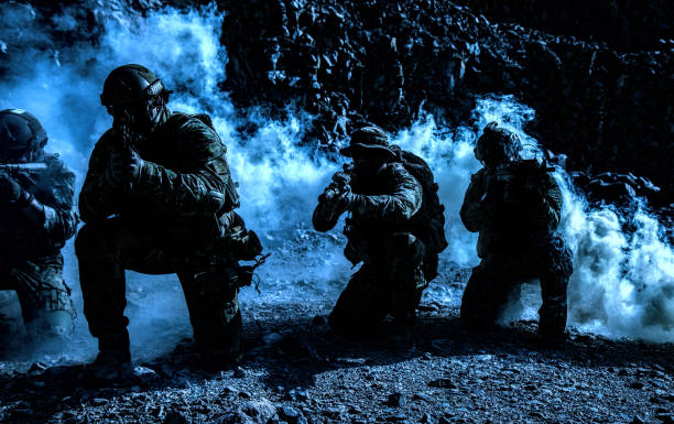 Squad in action Team squad of special forces in action in the desert among the rocks covered by smoke screen under cover of darkness battlefield stock pictures, royalty-free photos & images