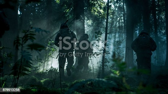 istock Squad of Five Fully Equipped Soldiers in Camouflage on a Reconnaissance Military Mission, Rifles in Firing Position. They're Running in Formation Through Dense Dark Forest. Side View Long Shot. 879913258