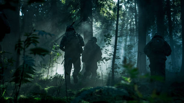 Squad of Five Fully Equipped Soldiers in Camouflage on a Reconnaissance Military Mission, Rifles in Firing Position. They're Running in Formation Through Dense Dark Forest. Side View Long Shot. stock photo