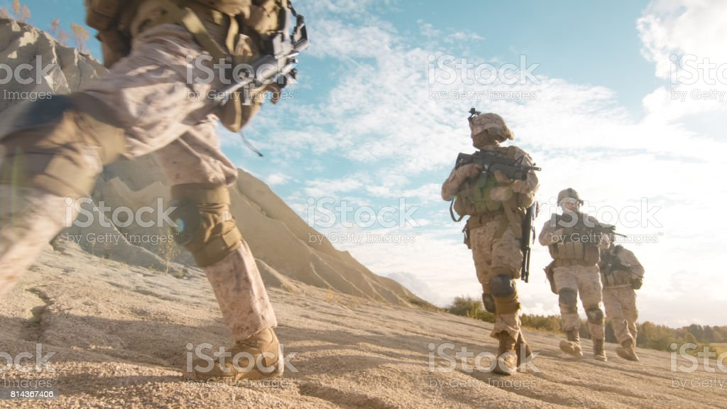Squad of Fully Equipped and Armed Soldiers Moving in Single File in the Desert. stock photo