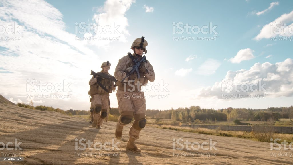Squad of Fully Equipped and Armed Soldiers With Comander Ahead Running in Single File in the Desert. stock photo
