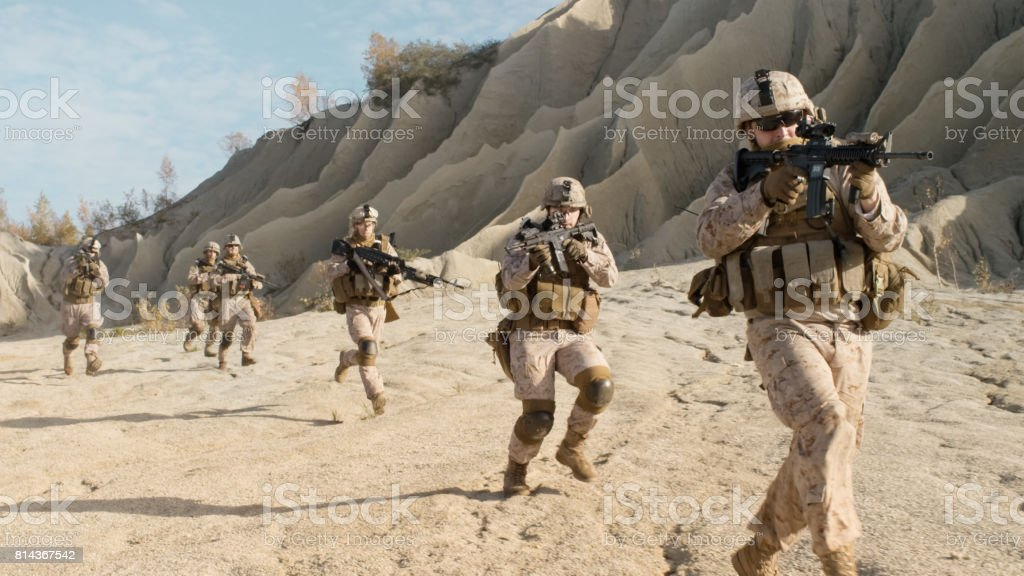Squad of Fully Equipped, Armed Soldiers Running in the Desert. Show Motion. stock photo