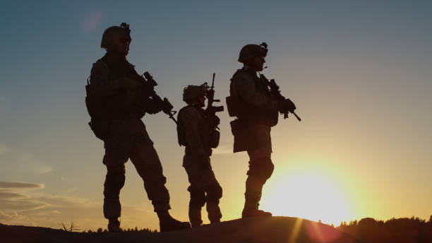 Squad of Three Fully Equipped and Armed Soldiers Standing on Hill in Desert Environment in Sunset Light. Squad of Three Fully Equipped and Armed Soldiers Standing on Hill in Desert Environment in Sunset Light. advanced tactical fighter stock pictures, royalty-free photos & images