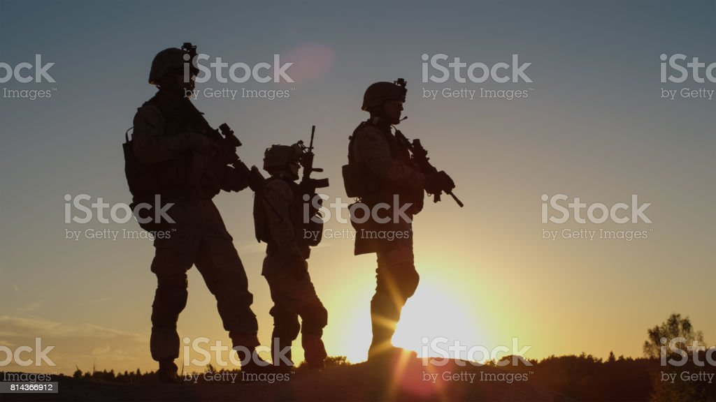Squad of Three Fully Equipped and Armed Soldiers Standing on Hill in Desert Environment in Sunset Light. stock photo