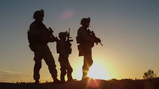 squad of three fully equipped and armed soldiers standing on hill in desert environment in sunset light. - armed forces stock photos and pictures