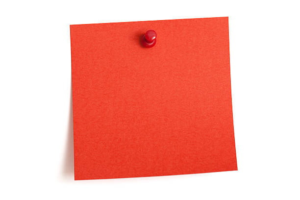 A square blank red note is pinned to a white wall