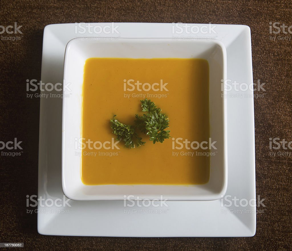 square bowl of carrot and ginger soup stock photo