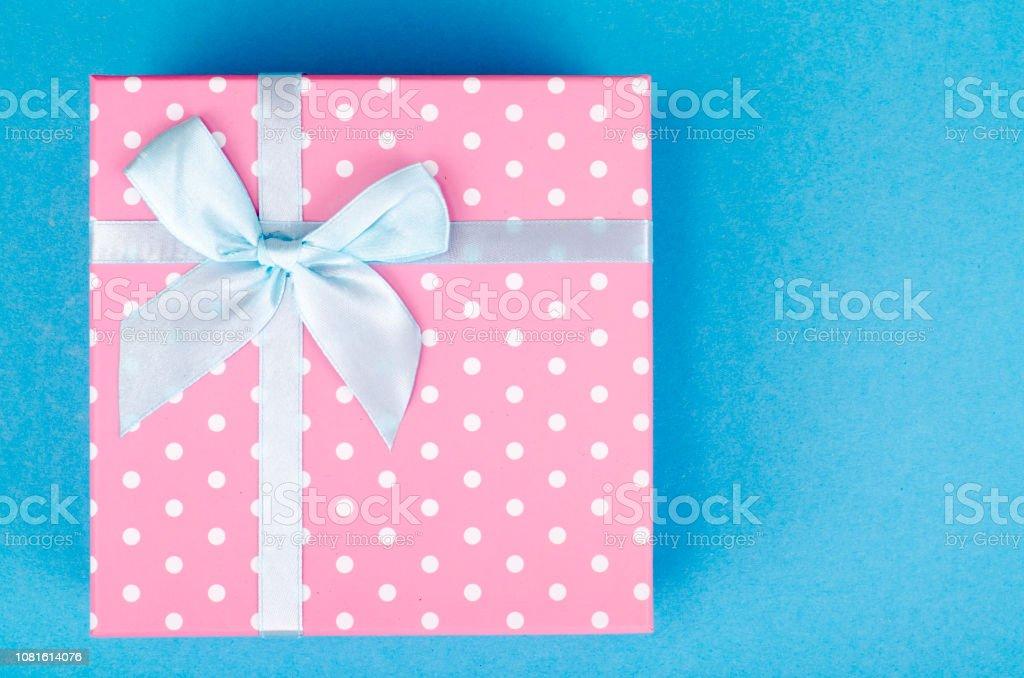 Square box of pink polka dots on bright background. Studio Photo