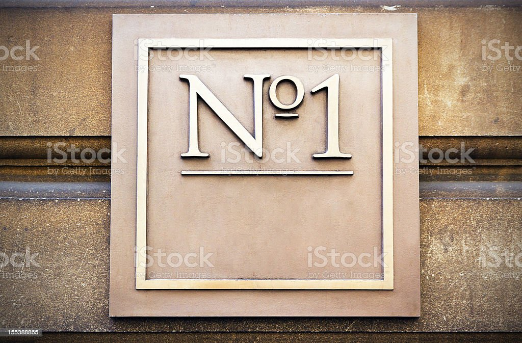 Square brass house number with 'No 1' copy space, vignette stock photo