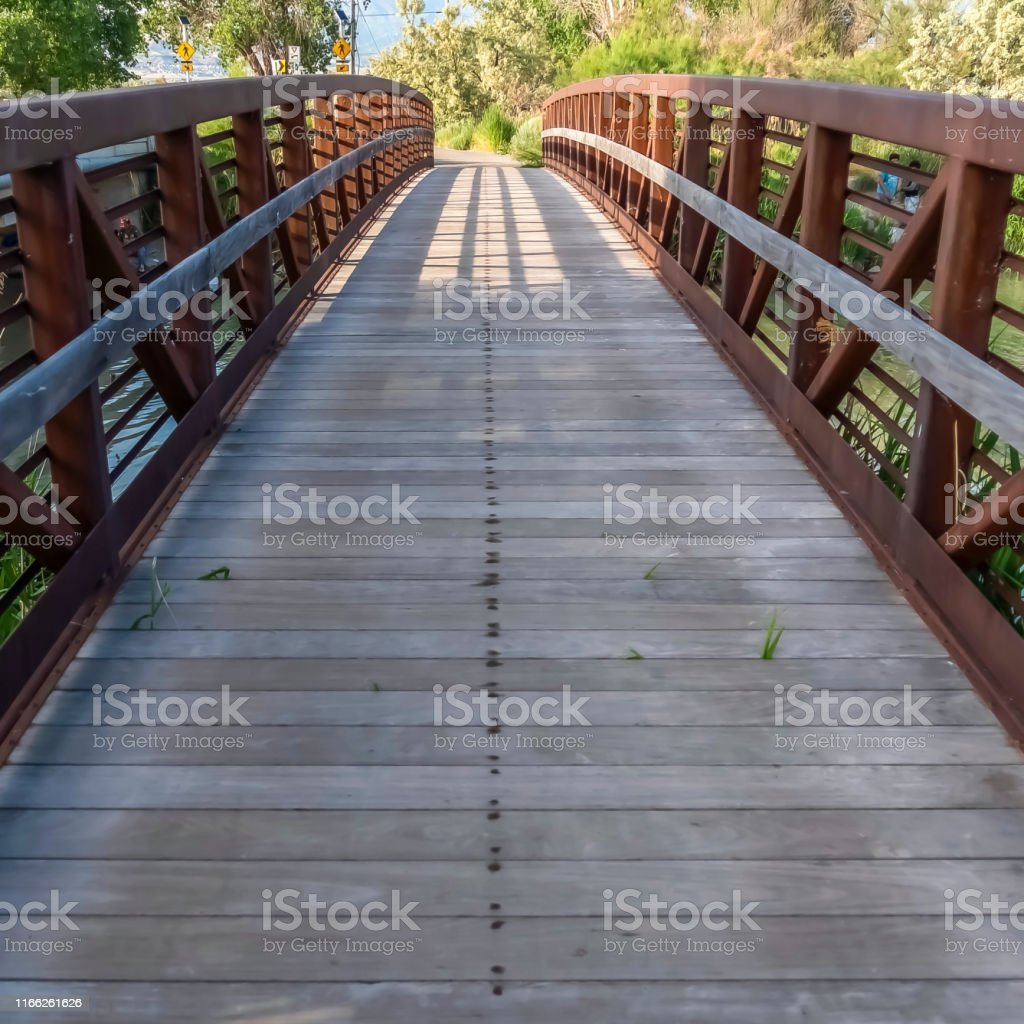 Square Bridge with wood deck and rusty metal railing over a lake with...