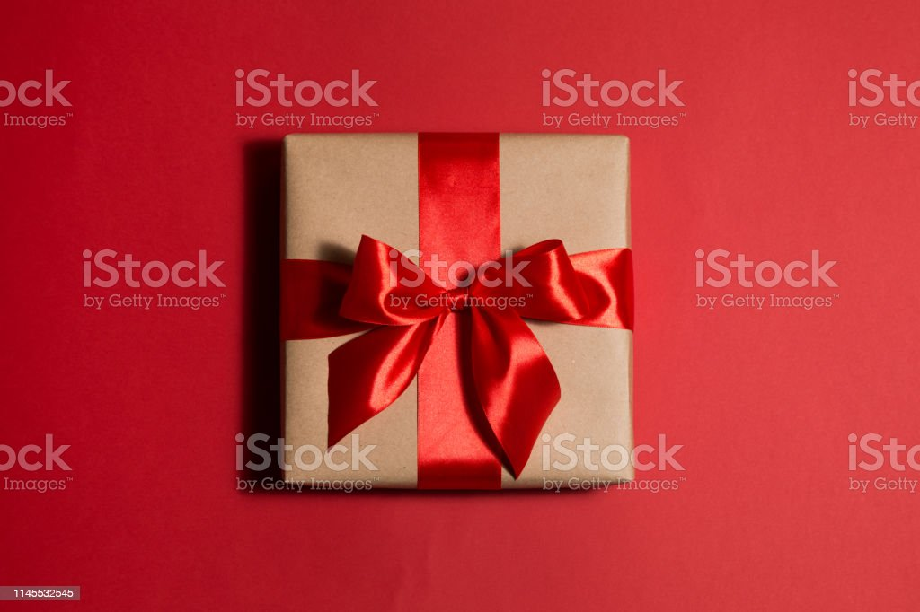 square craft box with gift tied with silk red ribbon on red...