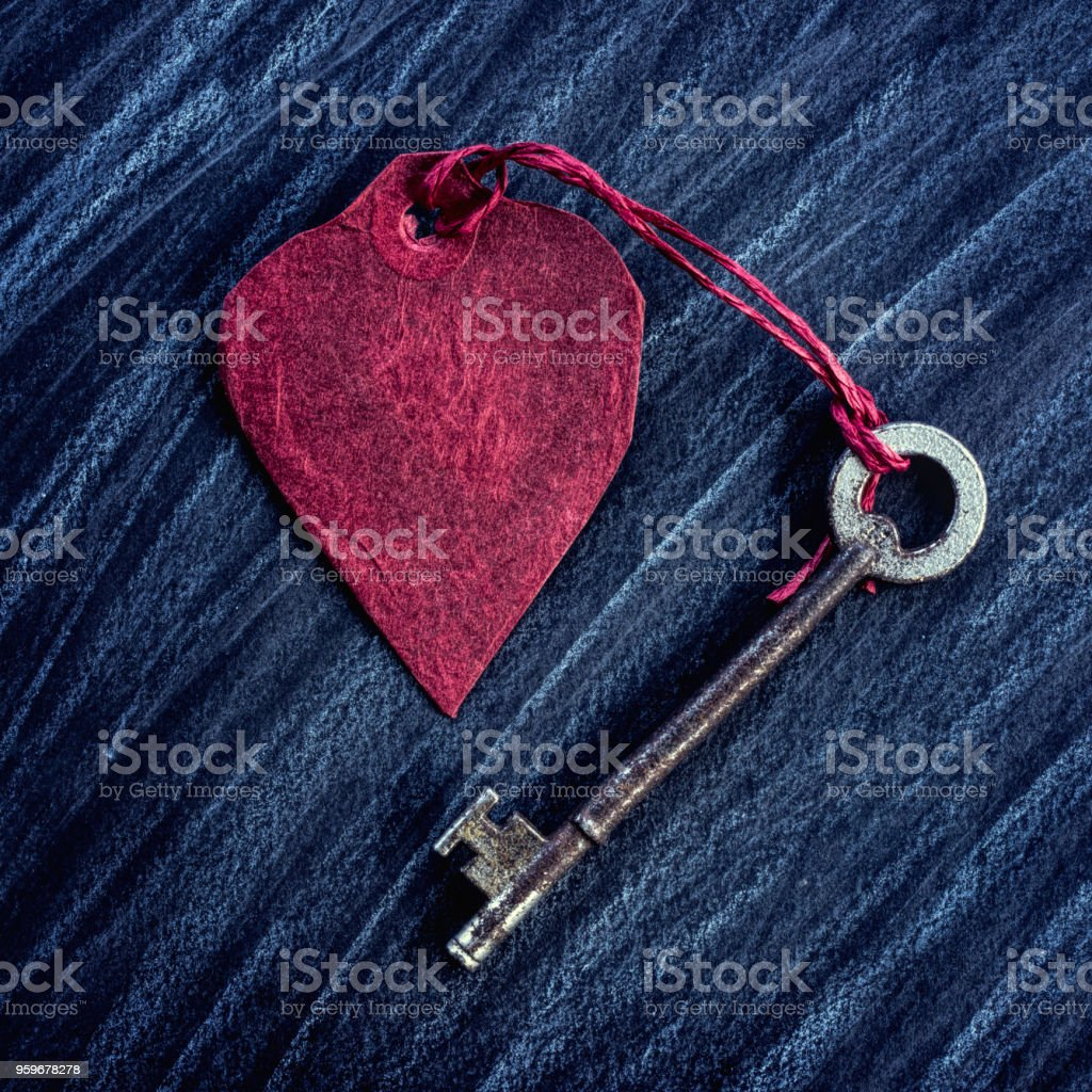Square Cropped Red Paper Heart tied to an old key stock photo