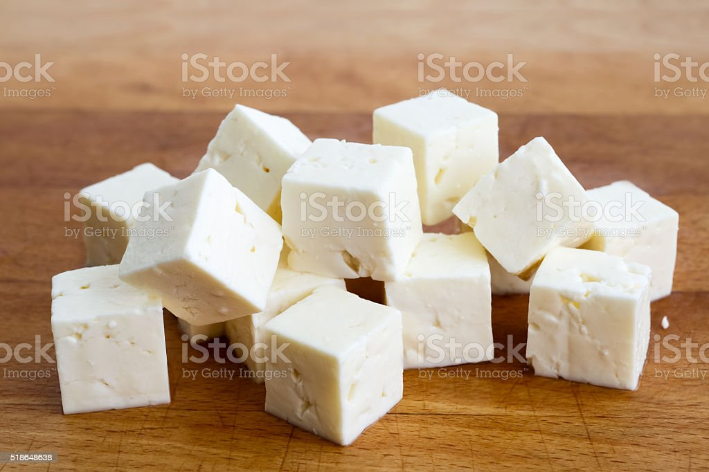 Square cubes of feta cheese isolated on wood board. stock photo