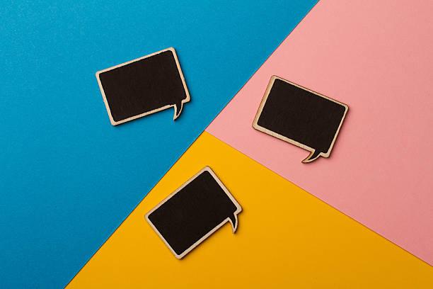 square empty chalk board speech bubbles on colored papers - einfache holzprojekte stock-fotos und bilder