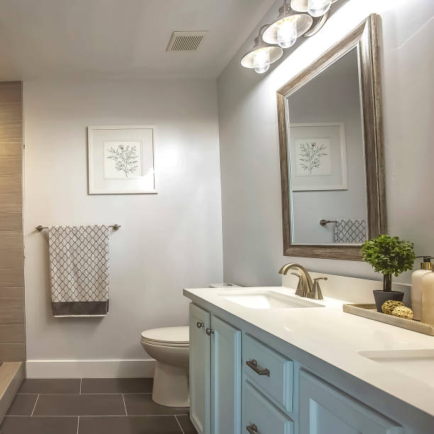 Square frame Bathroom interior with a bathtub in front of thee vanity area and mirror stock photo