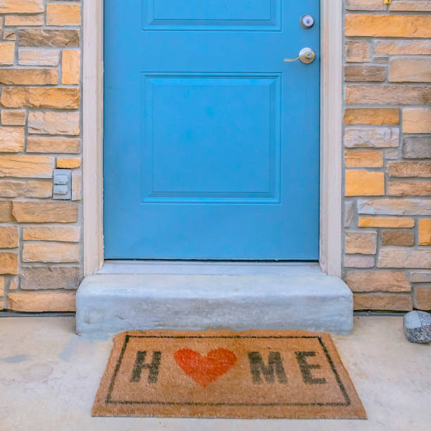 Square frame Entryway of a home with stairs leading to the porch and blue front door stock photo