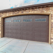 Square frame Large closed double wooden garage door in an ornamental face brick home with paved forecourt
