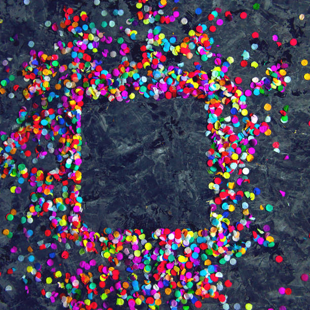 Square frame made of colorful confetti on black textured background. stock photo