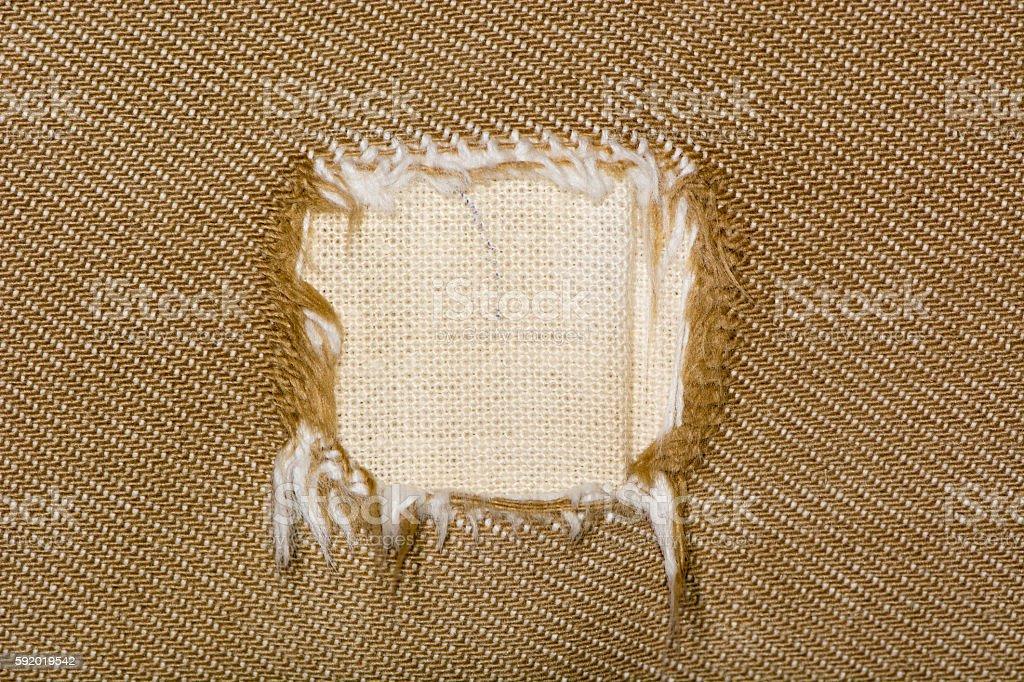 Square hole in fabric of sofa stock photo