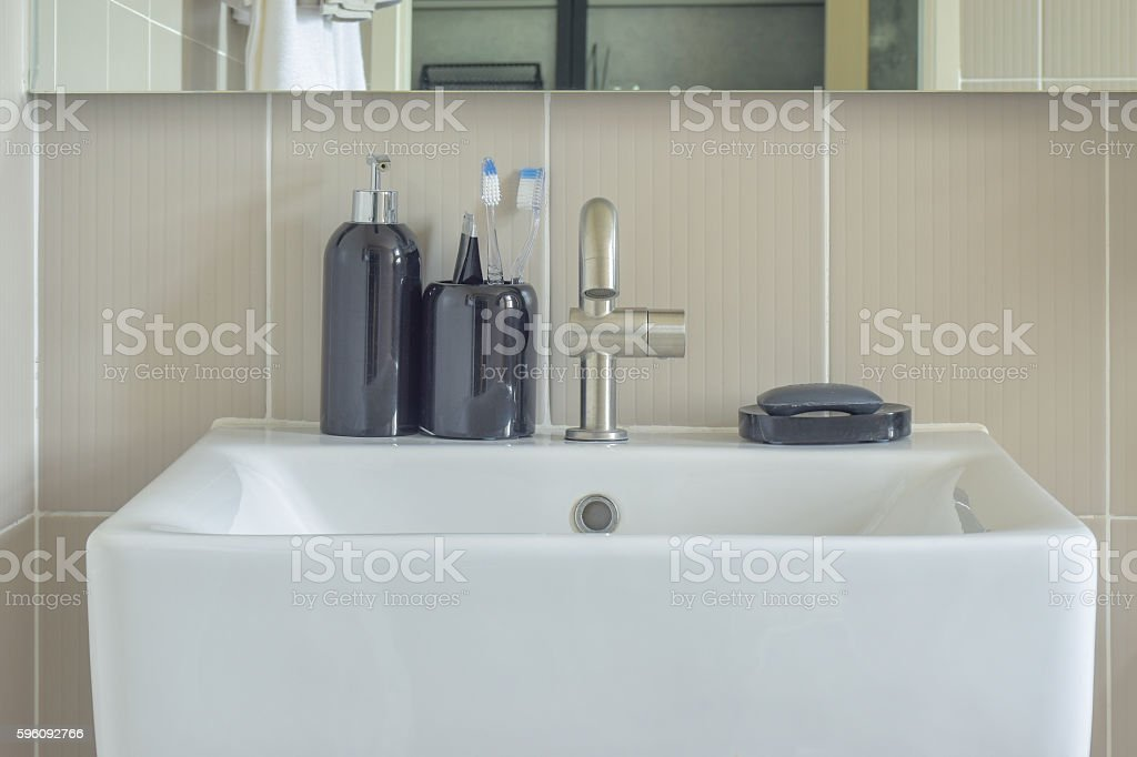Square lavatory and ceramic bottles in bathroom stock photo