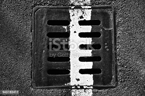 Square metal hatch in urban pavement, sewer manhole cover with marking lines.