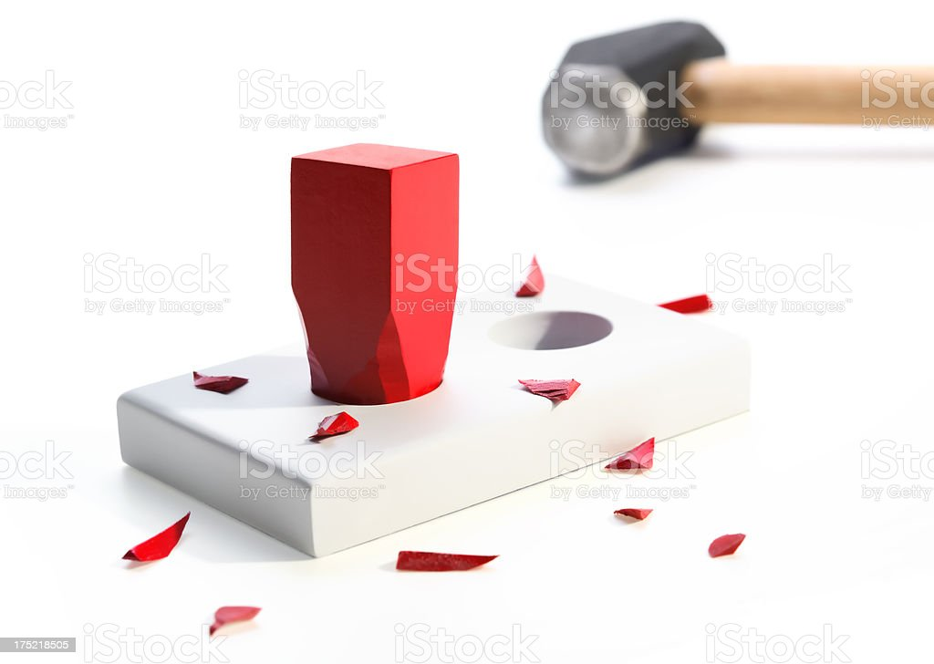 Square peg in a round hole with hammer stock photo