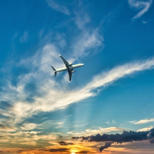 Square photo of big airplane above Kos island. Plane is captured from boat before landing. Sky is with sunset and dramatic clouds. stock photo