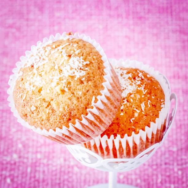 quadratischen foto. vanille-muffins mit kokos pulver. rosa hintergrund. kopieren sie raum. selektiven fokus. durchtrainierten bild. - vanille muffins stock-fotos und bilder