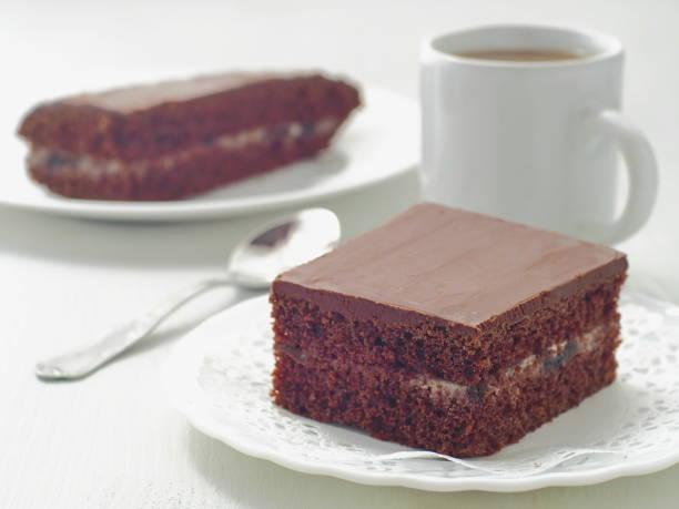 quadratische stück schokoladenkuchen mit cremefüllung - tarte und törtchen stock-fotos und bilder