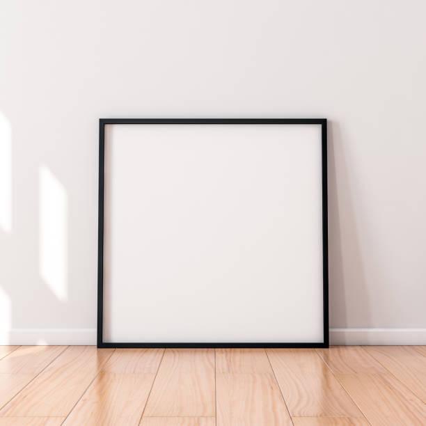 站在地板上的帶有黑色木制框架的方形海報 - 方形 個照片及圖片檔