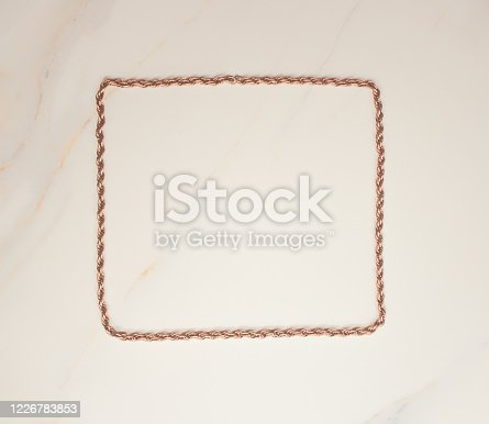 1058533662 istock photo Square uneven frame for text from a copper chain on white marble. Layout for blogger design. Minimal concept 1226783853
