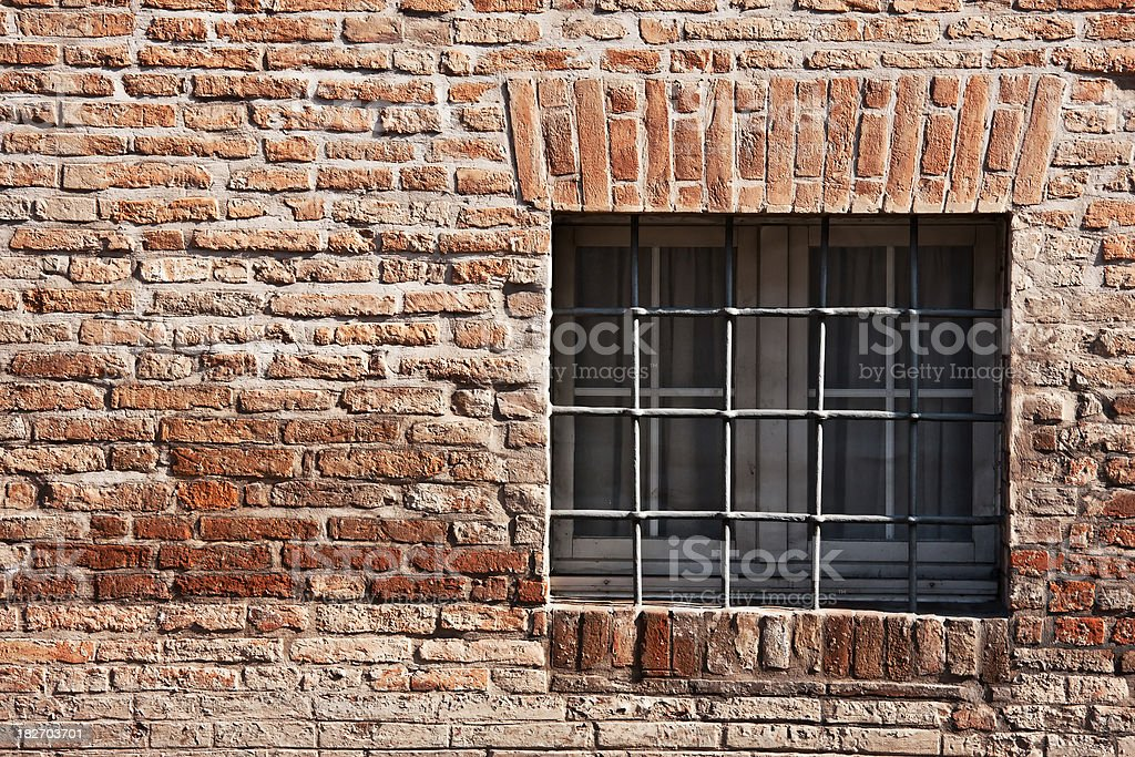 Square Window with Grid on an Old Brick Wall, Italy royalty-free stock photo