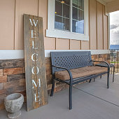 Square Wooden Welcome sign and furniture on the front porch of a residence. The exterior wall has a combination of wooden and stone brick sections.