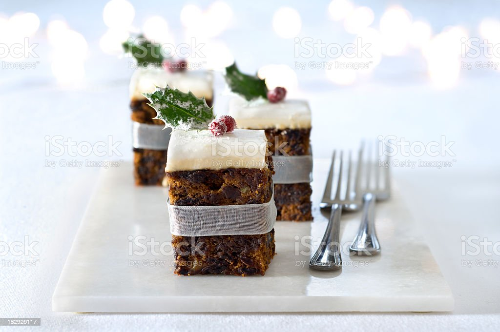 Squares of Christmas cake adorned with a cranberry stock photo