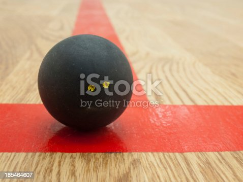 Double yellow dot official black squash ball on the red t-line in squash court