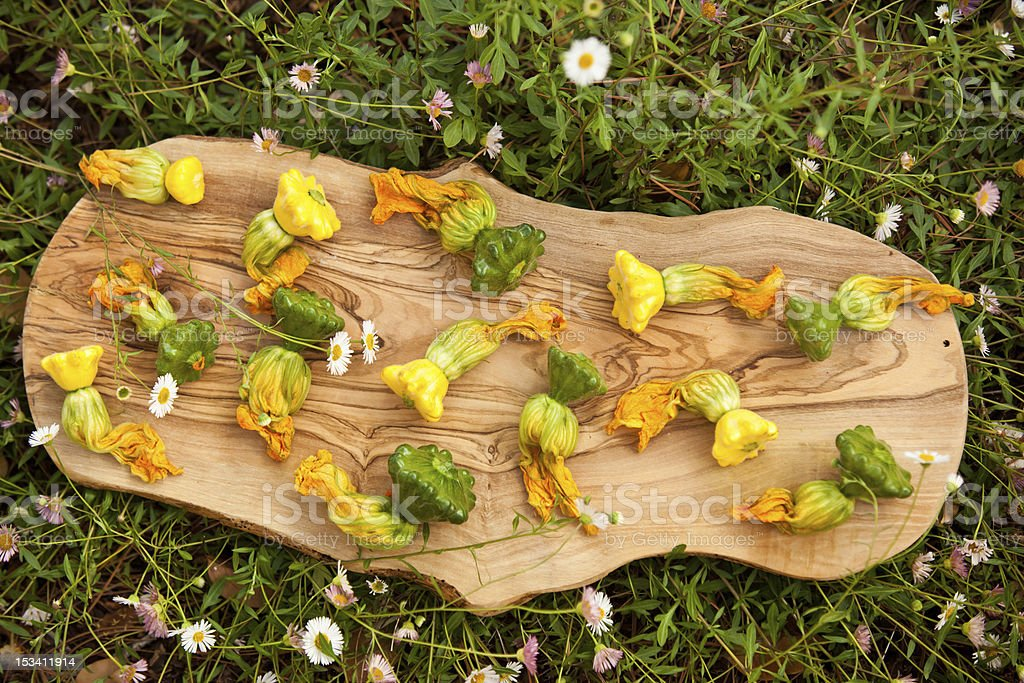 squash blossoms on wooden board with grass background royalty-free stock photo