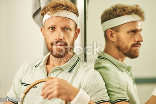Shot of a young man in the locker room after a game of squash