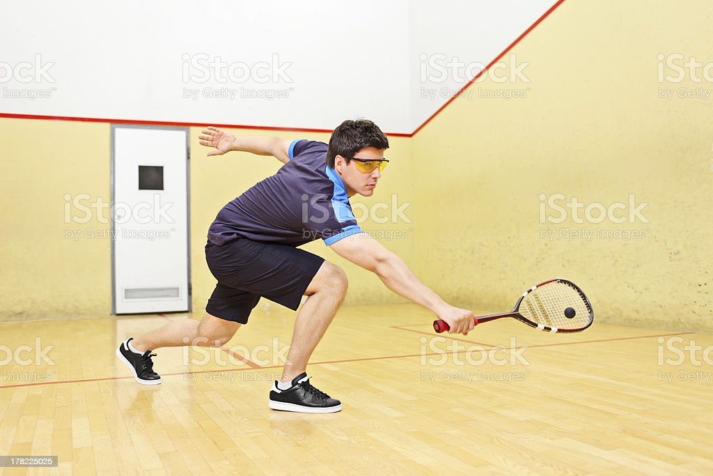 Squash player hitting a ball in court stock photo