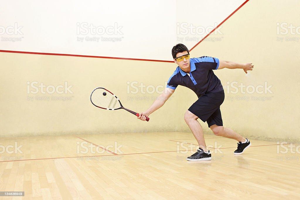 Squash player hitting a ball royalty-free stock photo