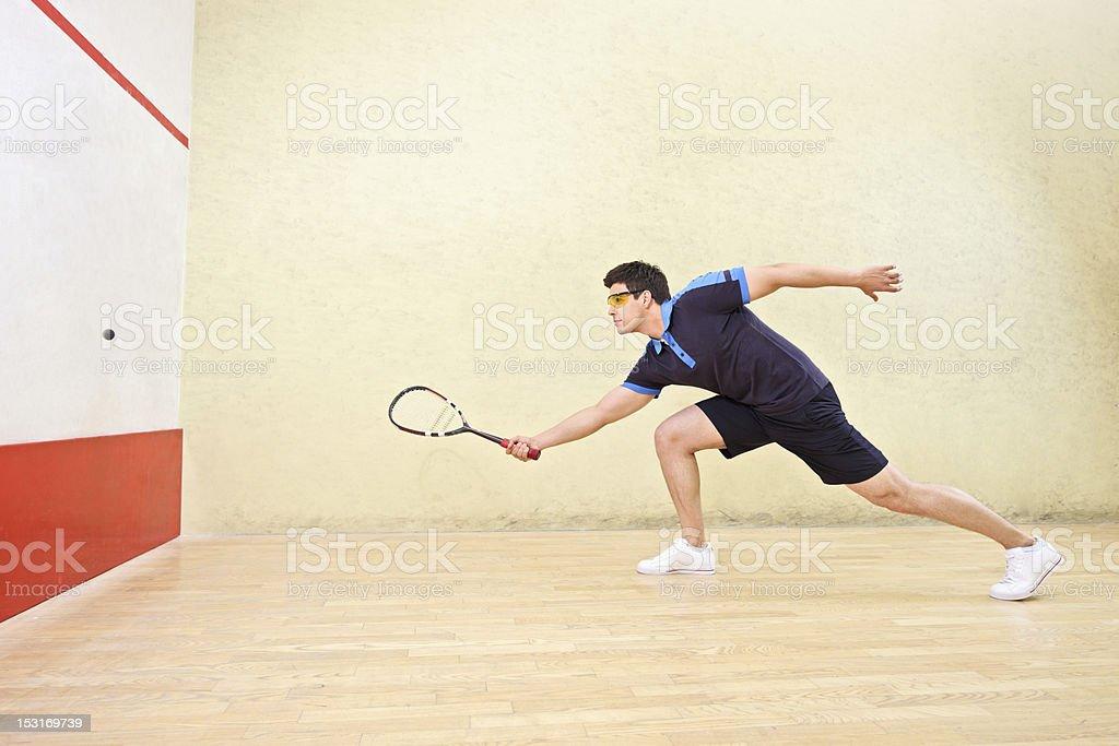 A squash player hitting a ball stock photo