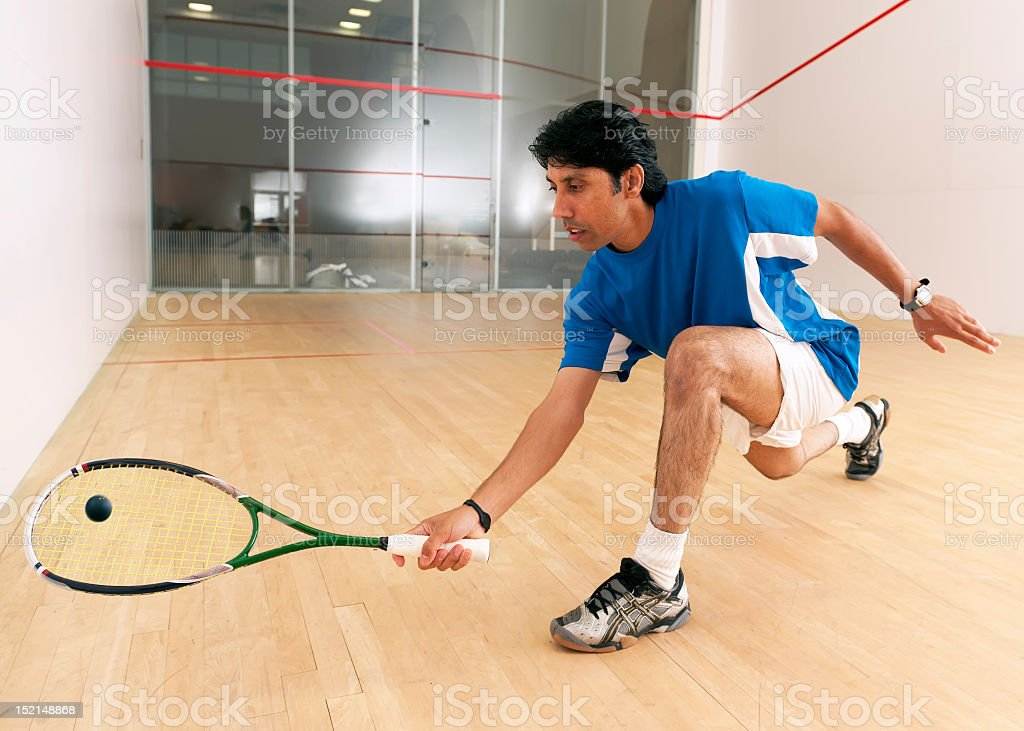 A squash player kneels down to hit a ball stock photo