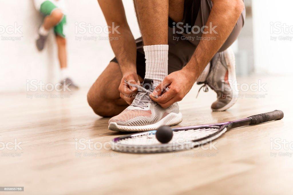 Squash player tying shoelaces stock photo