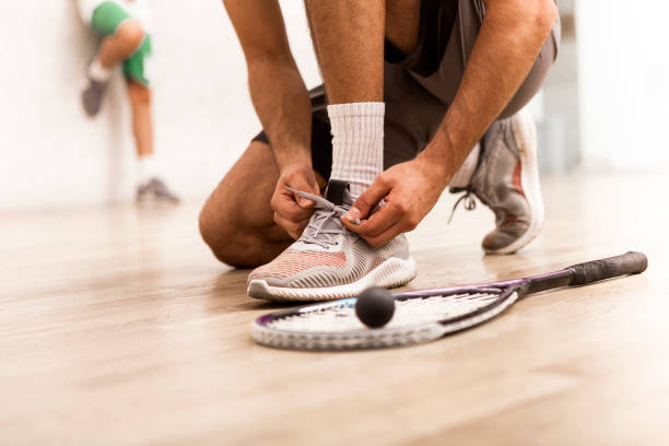 squash player tying shoelaces - racket sport stock pictures, royalty-free photos & images