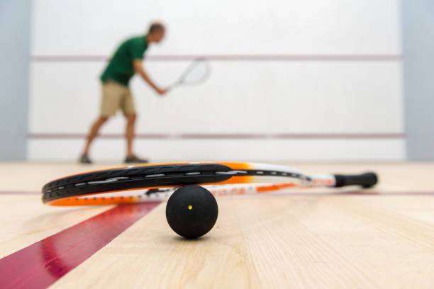 Squash racket and ball on a court floor stock photo
