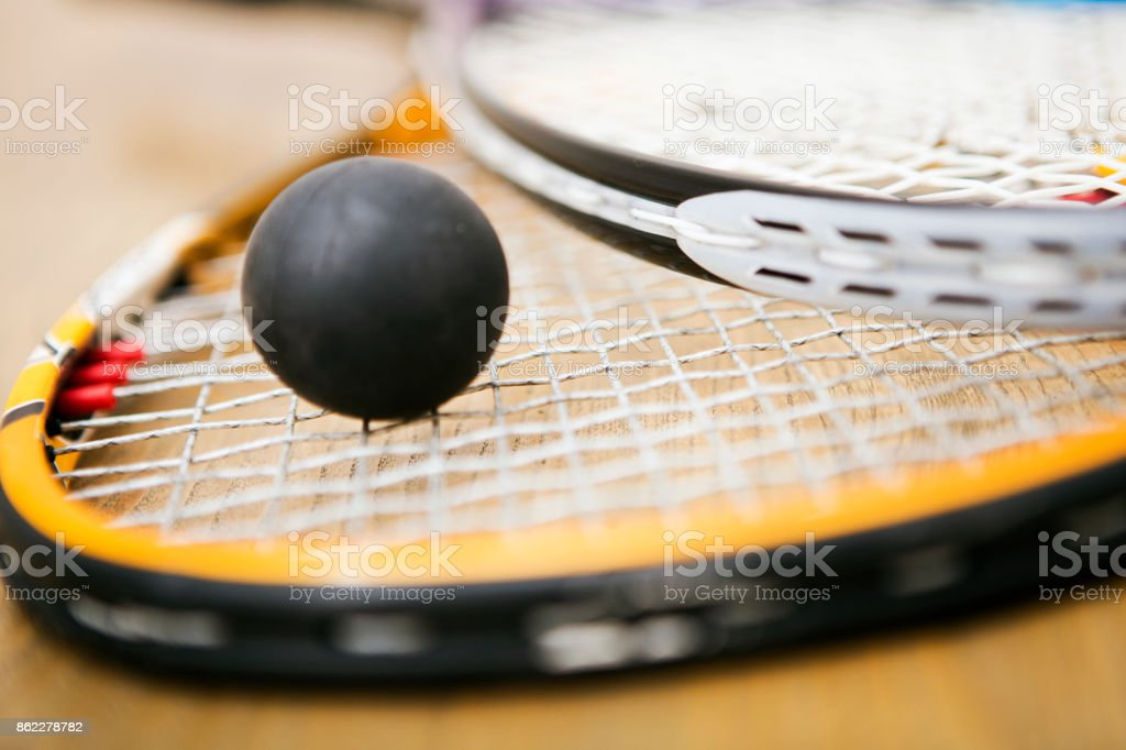 Squash racket and ball on the court close up stock photo