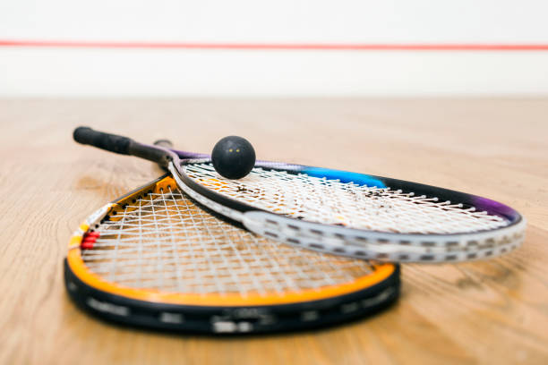 Squash racket and ball on the court ,leaning on wall stock photo